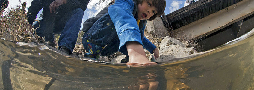 A child grasps a lamprey in a moment captured while filming The Lost Fish.